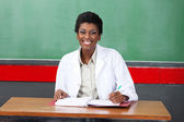 Happy Female Teacher With Pen And Binder Sitting At Desk — Stock Photo