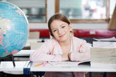 Cute Schoolgirl Smiling With Globe And Books At Desk — Stock Photo