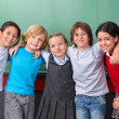 Cute Schoolchildren With Arms Around Standing Together In Classr — Stock Photo #27333457