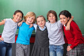 Cute Schoolchildren With Arms Around Standing Together In Classr — Stock Photo