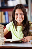 Happy Schoolgirl Sitting At Table In Library — Stock Photo