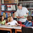Teacher Communicating With Students Sitting At Table In Library — Stock Photo