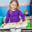 Girl Reading Book While Sitting On Desk At Kindergarten — Stock Photo