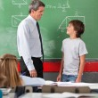 Teacher And Schoolboy Looking At Each Other In Classroom — Stock Photo
