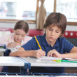 Little Boy Writing Notes With Classmate In Background — Foto de Stock