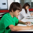 Schoolboy Studying At Desk In Classroom — Stock Photo