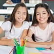 Schoolgirls Sitting At Desk In Classroom — Stock Photo