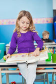 Girl Reading Book While Sitting On Desk At Kindergarten — Photo