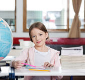 Cute Girl Smiling With Books And Globe At Desk — Stock Photo