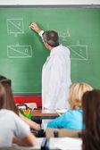 Teacher Writing On Greenboard While Teaching Students — Foto de Stock