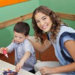 Stock Photo: Teacher With Student Painting In Classroom