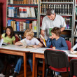 Teacher Showing Book To Schoolboy In Library — Stock Photo #27427837