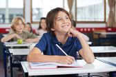Schoolboy Looking Up While Studying At Desk — Stock Photo