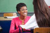 Teacher Looking At Teenage Schoolgirl At Desk — Stock Photo