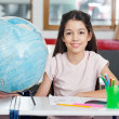 Schoolgirl Smiling With Globe And Organizer At Desk — Stock Photo