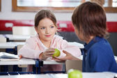 Little Girl Giving Apple To Boy In Classroom — Stock Photo