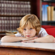 Bored Schoolboy Leaning On Table In Library — Stock Photo