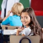 Schoolgirl Sitting At Desk In Classroom — Stock Photo #27523353
