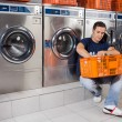 MWith Basket Of Clothes Sitting At Laundromat — Stock Photo #27524591