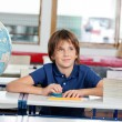Schoolboy Looking Away With Globe And Books At Desk — Stock Photo