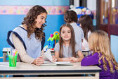 Girl With Teacher And Friend In Classroom — Stock Photo