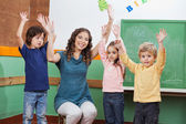 Teacher And Children With Hands Raised In Classroom — Stock Photo