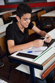 Schoolboy Copying From Cheat Sheet At Desk — Stock Photo