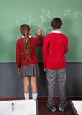 Teenage Schoolchildren Writing On Board — Stock Photo