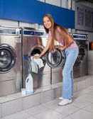 Woman Putting Clothes In Washing Machine — Stock Photo
