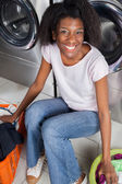 Happy Woman Sitting In Laundry — Stock Photo