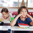Bored Schoolboy Looking Away Sitting At Desk In Classroom — Stok Fotoğraf #27597489