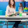 Teacher Writing In Book With Girl Playing In Background — Stock Photo