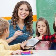 Teacher And Children Playing With Xylophone In Classroom — Stock Photo #27598509