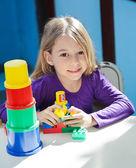 Girl Sitting With Toys At Desk In Preschool — Stockfoto