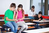Teenage Schoolchildren Listening Music In Classroom — Stock Photo