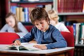 Skolpojke läsa boken på bordet i biblioteket — Stockfoto