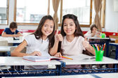 Happy Schoolgirls Gesturing Thumbs Up At Desk — Stock Photo