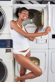Woman Standing By Dryer In Laundry — Stockfoto