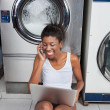 Stock Photo: WomUsing Laptop And Mobilephone In Laundry