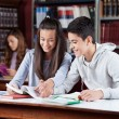 Teenage Couple Studying Together In Library — Stock Photo