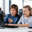 Boy Pointing While Using Desktop Pc With Friend At Desk — Stock Photo