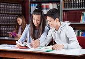 подростковая пара, изучение вместе в библиотеке — Стоковое фото