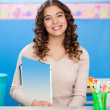 Stock Photo: Teacher Holding Book While Sitting At Desk