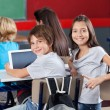 Schoolchildren With Digital Tablet Sitting In Classroom — Stock Photo #27765135