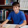 Stock Photo: Teenage Male Student Sitting At Table In Library