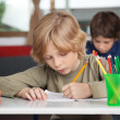 Stock Photo: Schoolboy Writing In Book At Desk