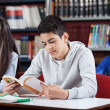 Teenage Schoolboy Reading Book In Library — Stock Photo #27765921