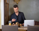 Businessman Messaging On Mobilephone While Having Meal In Cafe — Stock Photo