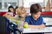 男孩在桌子在教室里学习 — 图库照片