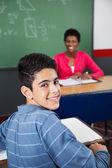 Happy Teenage Schoolboy Sitting At Desk — Stock Photo